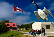 group of people sitting at the base of a large white goose monument with Canada flag flying nearby