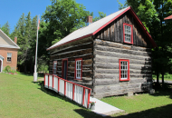 log cabin with red and white windows and porch