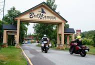 2 motorcycles riding under an archway with sign Best Northern Resort