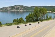 scenic view of  motorcycles riding down a winding road with water and cliff in the background