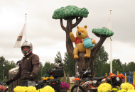 motorcycle rider with motorcycles standing in front of winnie the pooh and tree statue