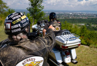 2 motorcycle riders sitting on their bikes, overlooking a scenic view