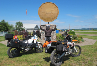 man standing in front of big loonie with 2 motorcycles