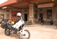 white motorcycle in foreground with rider sitting at an outdoor table under a coffee shop sign