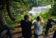 a couple standing behind a fence, overlooking a beautiful waterfall  with forest framing the picture