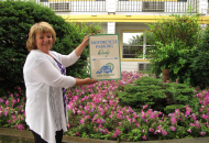 woman wearing a white sweater, holding a sign standing in front of flower garden with pink petunias