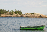 green aluminum boat anchored in water with smooth rock face behind