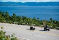 2 motorcycles riding down a scenic road with lake and hills in background
