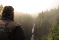 motorcycle rider overlooking waterfall with forest on either side