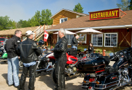 group of riders with motorcycles in front of restaurant
